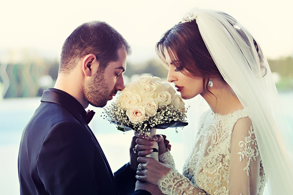 Just married couple with bouquet of roses