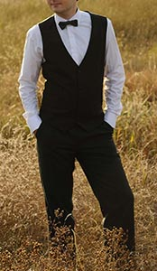 Groom In a vested suit posing in the field