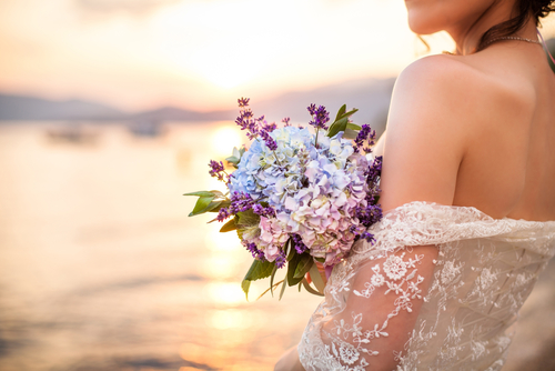 Sunset with woman in wedding dress holding flowers
