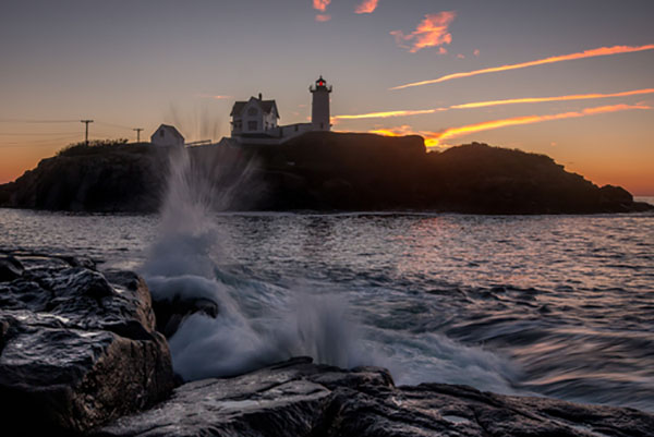 Waves crashing in front of lighthouse