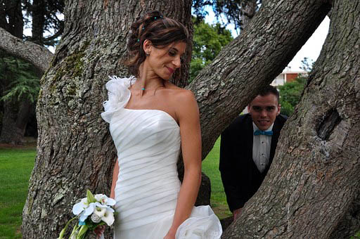 Bride and groom posing by tree