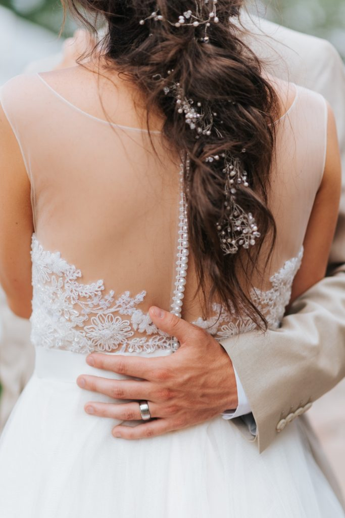 Bride with grooms arm around her back
