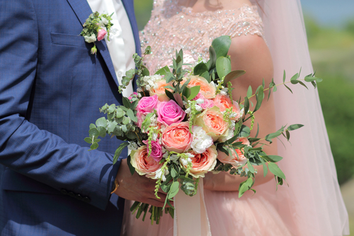 bride and groom embrace holding bouquet