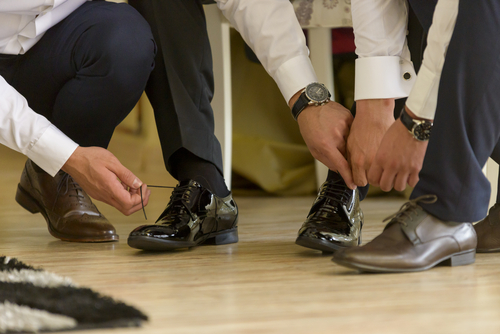 business men tying their dress shoes
