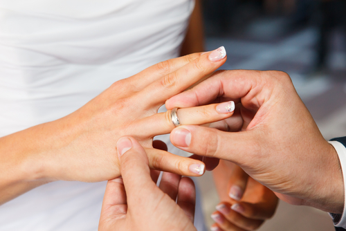 man placing wedding band on woman