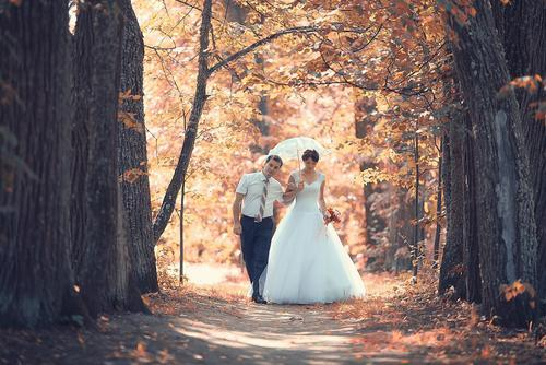 Bride and groom under fall trees