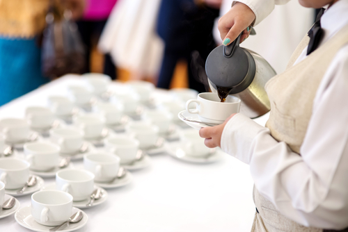 Hotel breakfast service - waitress pouring coffee for guest